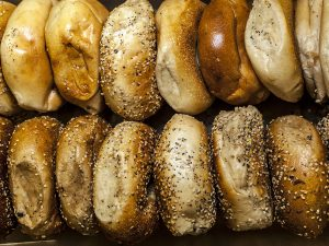 Two rows of Bruegger's Bagels coated with sesame seeds